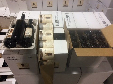 Hand labeling wine bottles.
