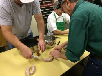 Twisting and cutting links of fresh sausage.