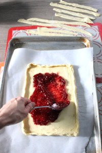 Smearing raspberry jam onto puff pastry