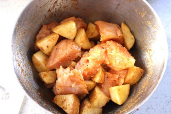 Add spices to the cubed chicken and potatoes