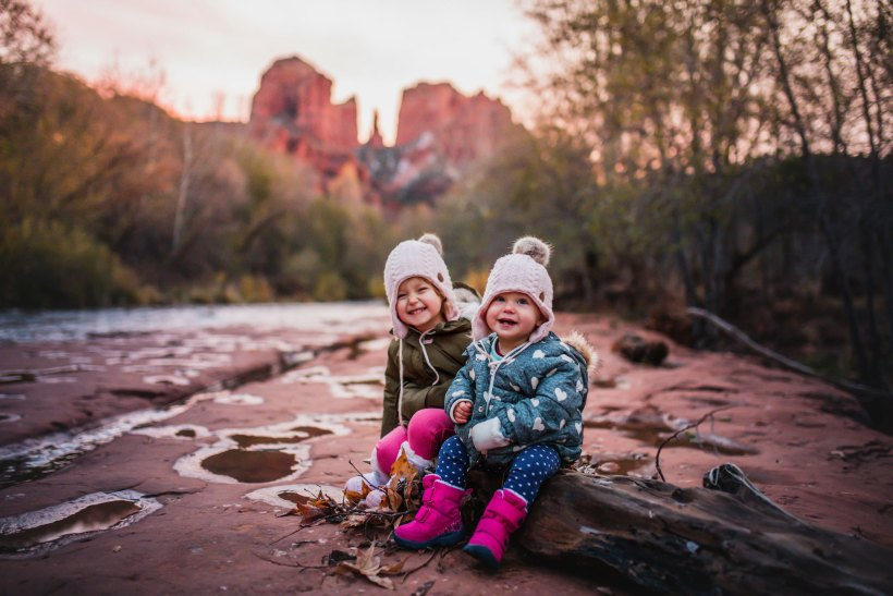 Two kids sitting on a log at Red Rock Crossing Trail
