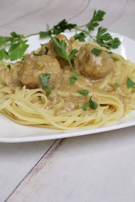 A plate of linguini with a creamy gravy and meatballs.