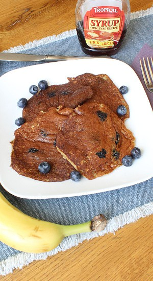 A stack of 4, each pancake has protein powder, banana, and fresh blueberries.