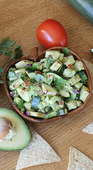 A serving bowl full of avocado, tomato, and zucchini.