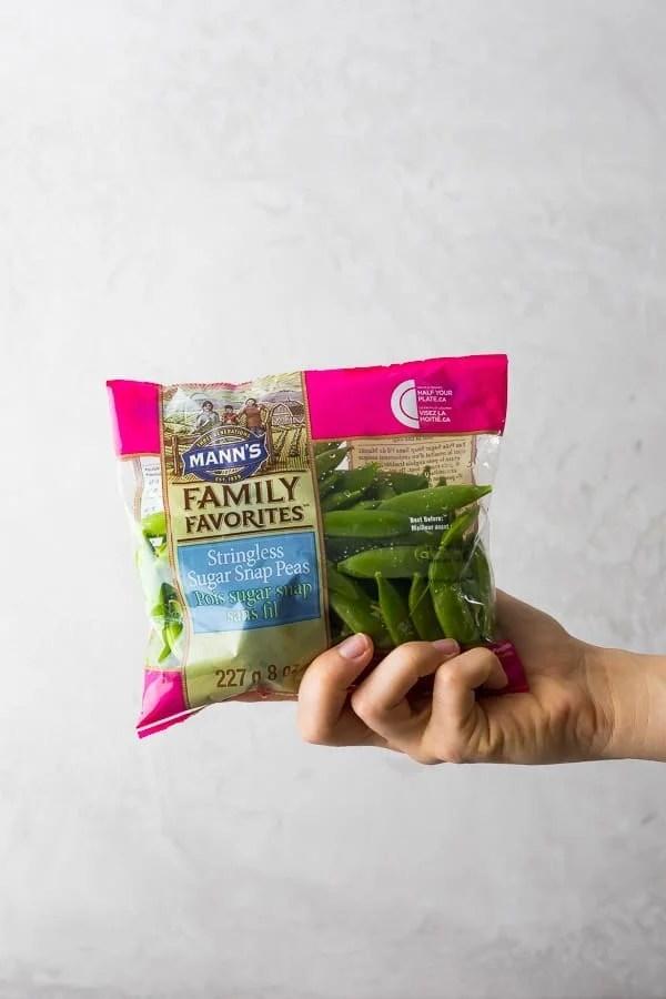 hand holding bag of stringless sugar snap peas