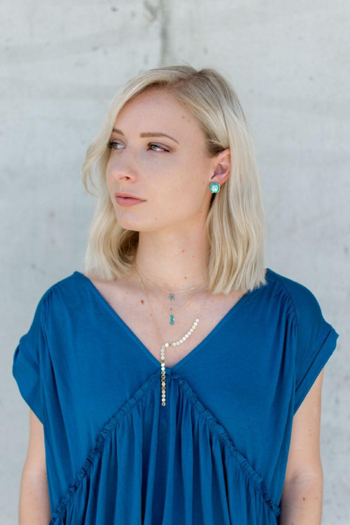 Jenny Bess wearing light blue jewelry and dark blue blouse