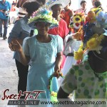 Girl in blue dress waving, with flowered bonnet and basket at special needs children Easter Bonnet parade at Queen's Park Cricket Club, color eggs, Sweet T&T, Sweet TnT, Trinidad and Tobago, Trini,