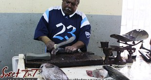 Fishmonger cleans a fish for a waiting customer at the Tunapuna Market in sweet T&T for Sweet TnT Magazine, Culturama Publishing Company, for news in Trinidad, in Port of Spain, Trinidad and Tobago, with positive how to photography.
