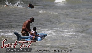 Grandfather and grandson in sea water using inflatable shark toy at Chaguaramas Beach in Sweet T&T, Sweet TnT Magazine, Trinidad and Tobago, Trini, vacation, travel Chaguaramas Boardwalk