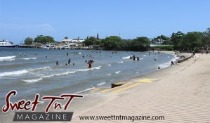 Wavy sand, blue sky, sea, people bathing, boats in water, in Sweet T&T, Sweet TnT Magazine, Trinidad and Tobago, Trini, vacation, travel Chaguaramas Boardwalk