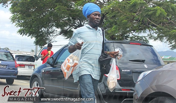 Nuts vendor selling salt, fresh, roasted peanuts on the streets in between vehicles at red traffic light in sweet T&T for Sweet TnT Magazine, Culturama Publishing Company, for news in Trinidad, in Port of Spain, Trinidad and Tobago, with positive how to photography.