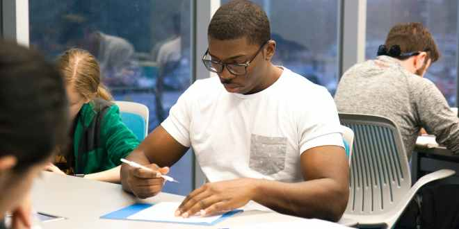 CXC/CSEC exam tips for students ready or not, man in white crew neck t shirt sitting on chair while holding white pen