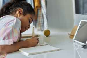 Online classes. Photo of girl writing on white paper.