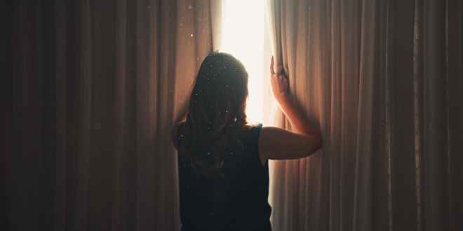 Mental Health during Covid. Unrecognizable woman opening window curtain in shining daylight.
