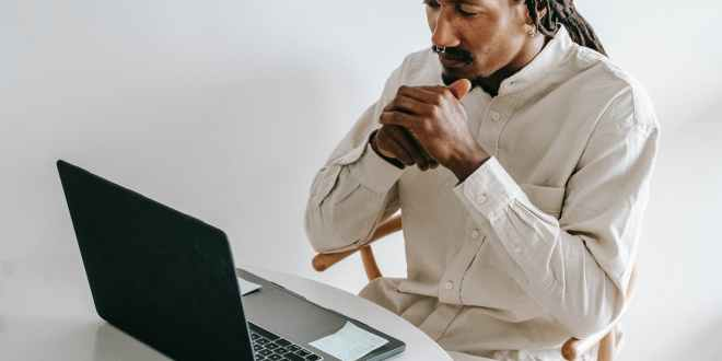 Starting a business, serious black man working on laptop in light room