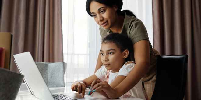 Cheap laptops. Mother helping her daughter use a laptop.