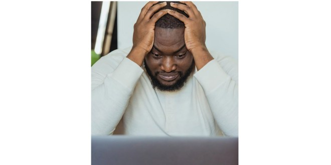 Writer's block. Sad black man with hands on head near laptop
