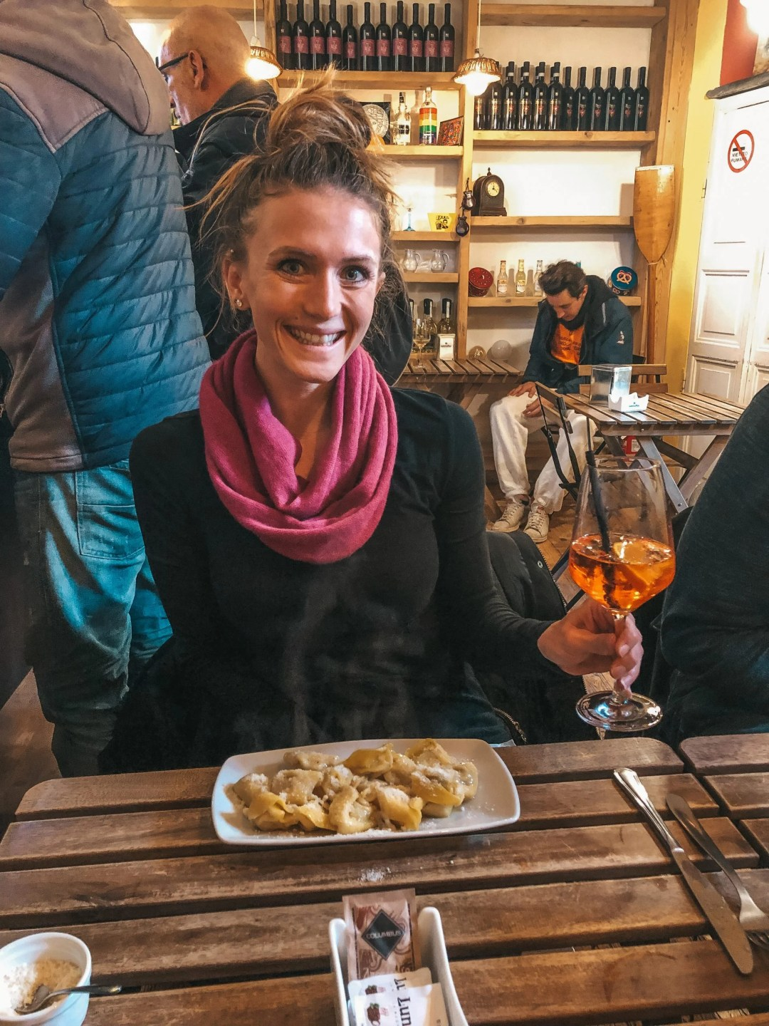 woman holding aperol spritz drink in front of a plate of ravioli