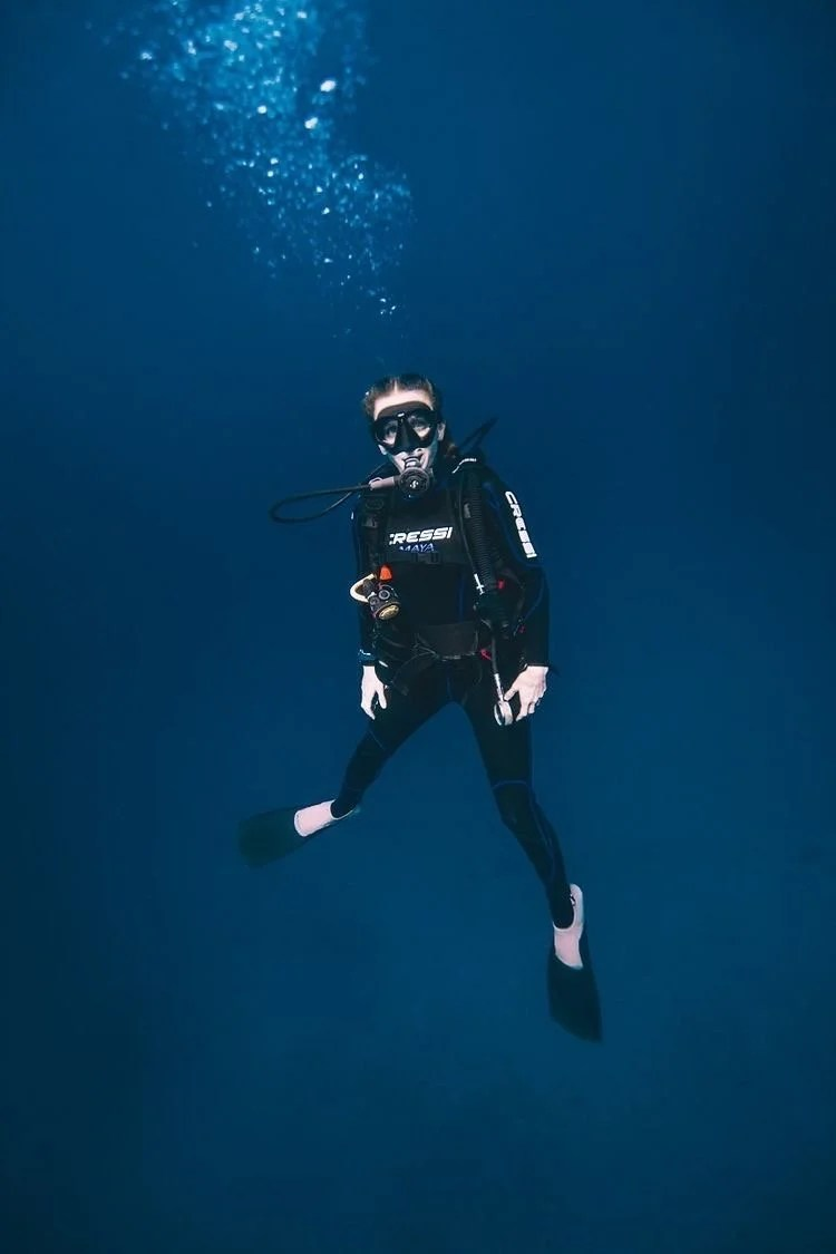 woman scuba diving with dark blue ocean backdrop