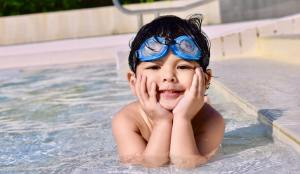 Boy Smiling in pool - pool safety