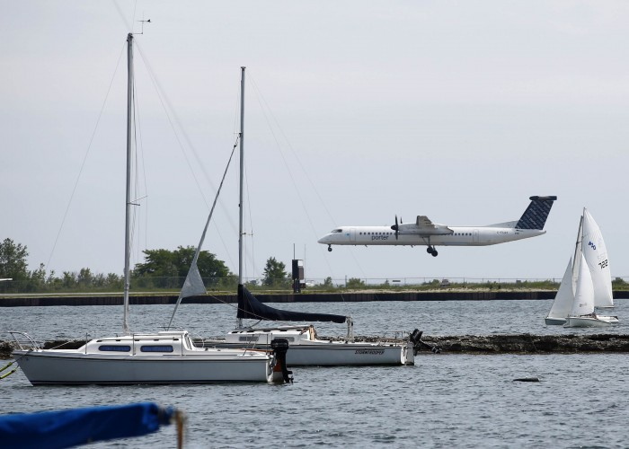Jul 9, 2015; Toronto, Ontario, Canada; An airplane lands at Billy Bishop Toronto City Airport across the Western Channel in preparation for the 2015 Pan Am Games. Mandatory Credit: Rob Schumacher-USA TODAY Sports