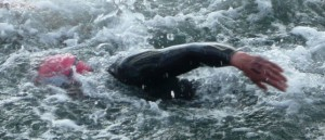 Næsten strakt arm under fremførding ved svømning med våddragt