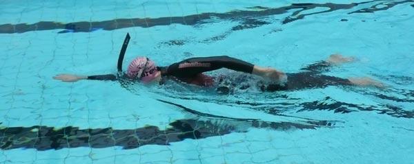 Svømmer, der svømmer crawl med snorkel og våddragt
