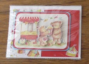 Children's greeting card featuring two teddy bears. One is buying popcorn from the other teddy, who has a popcorn stall. Teddy bears are in raised card above the background picture.