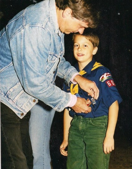 Cole earns a badge as a Cub Scout. But check out those green jeans!