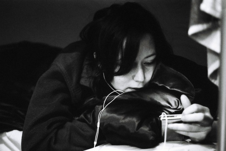 Black and white image of a young women listening to music while laying on a bed.