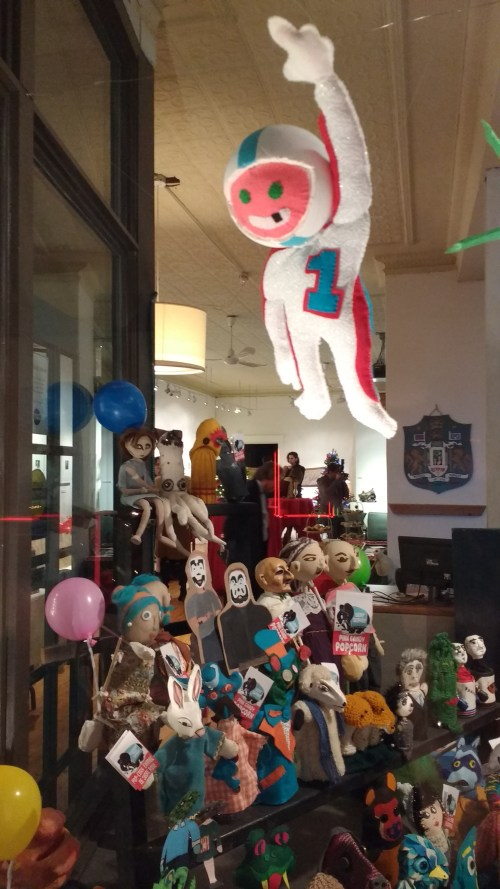 The Human Cannonball soars over the crowd. The Puppet-A-Go-Go audience has been given boxes of Lucky Elephant Pink Popcorn and balloons for this month's circus installation.