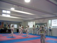 Students spar in the main dojang during testing.