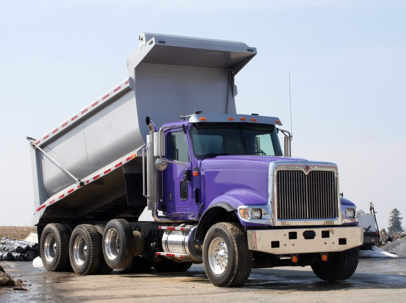 This purple dump truck has a purple cab and a silver dump area. It looks brand new.