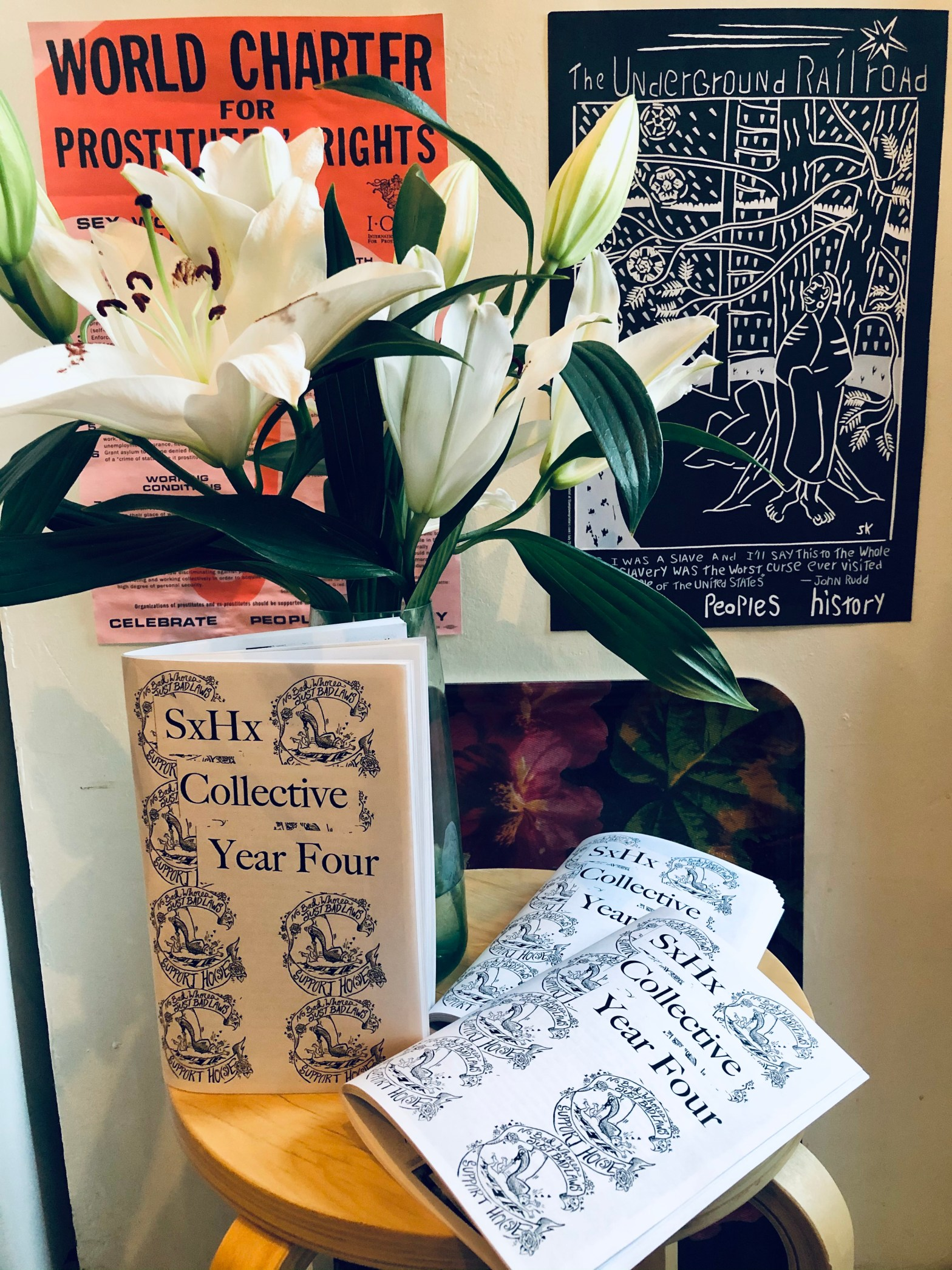 three zines displayed near white lilies with posters in the background