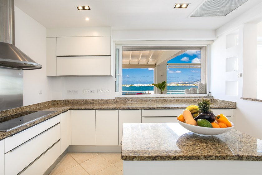 white kitchen with a view of the simpson bay lagoon