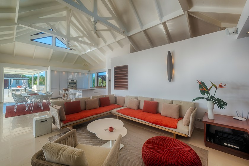 living room area at villa turtle nest in baie longue st martin with low white couch and orange cushions