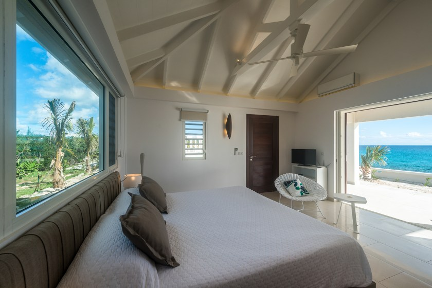 Windows on the left and ocean view through the door on the right with a bed in the middle at villa turtle nest in saint martin