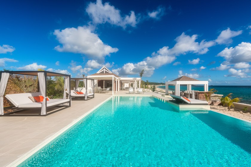 outdoor pool at villa turtle nest with pool loungers on the left
