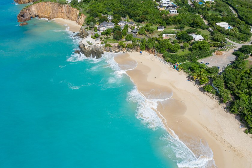 drone photo of a blue ocean with the beach on the right at baie rouge beach in terres basses st martin