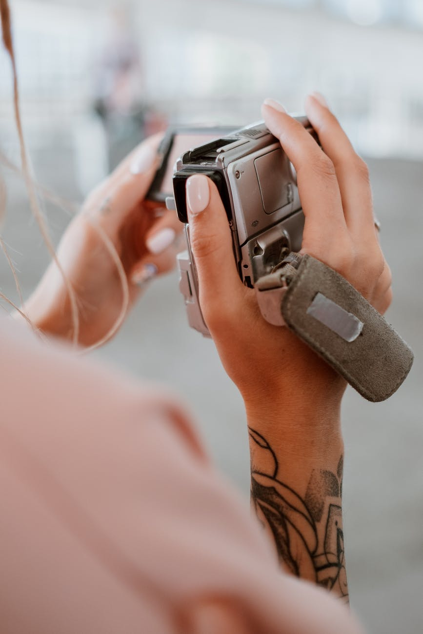 person holding a silver camera