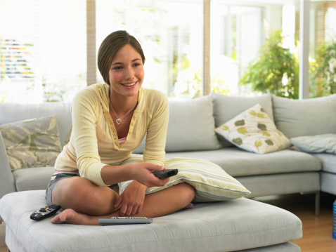 Teenage girl (14-16) watching television, smiling