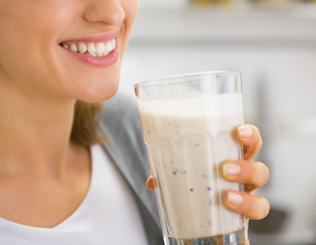 Closeup on young woman drinking smoothie