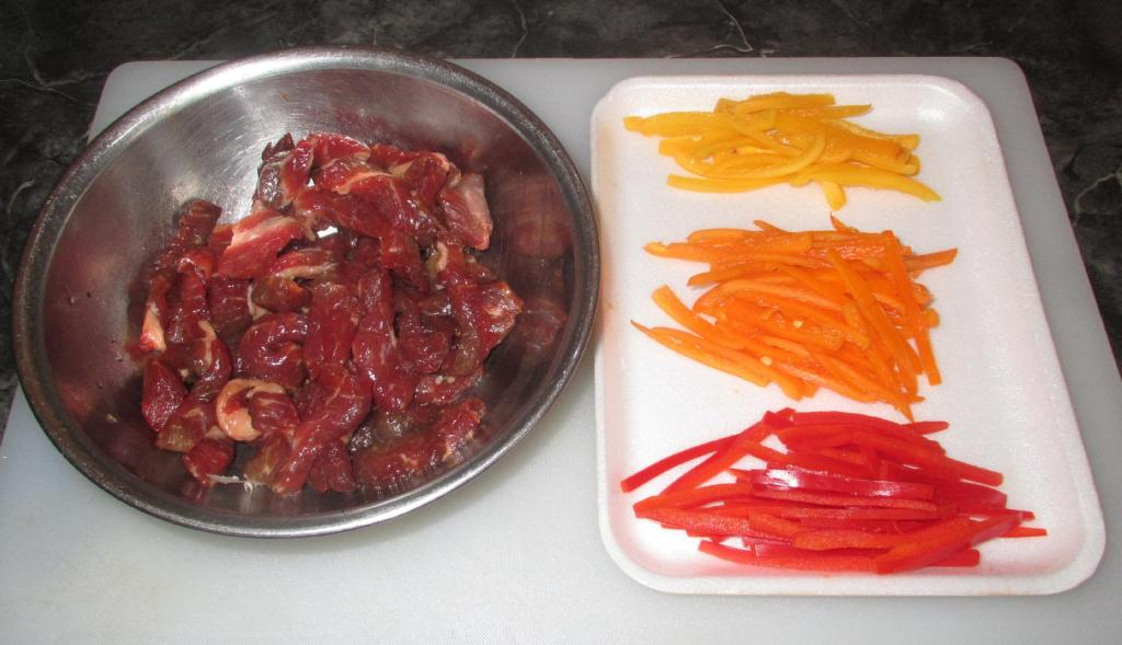 Beef strips marinating alongside strips of Bell Peppers