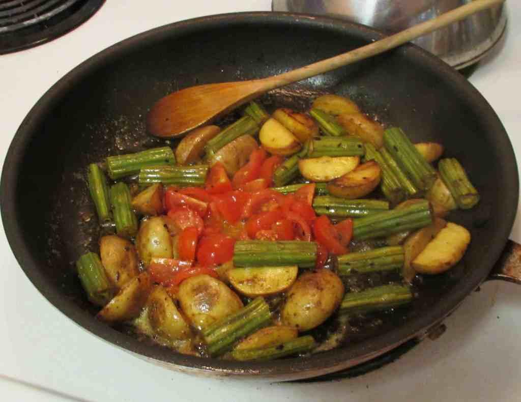 Finishing cooking a Drumstick Potato Masala
