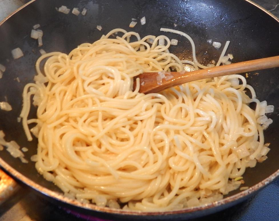 Coating Cooked Pasta with an Aromatic Butter mix.