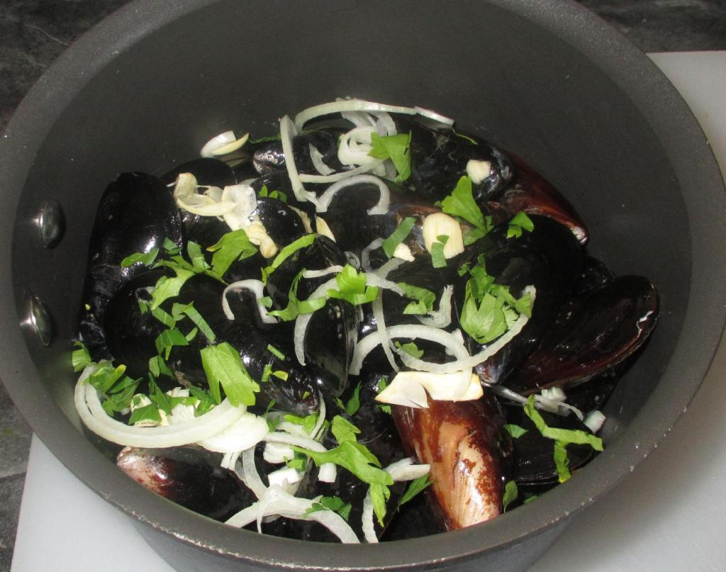 Layering fresh Mussels in a pot with Onion, Garlic and Parsley