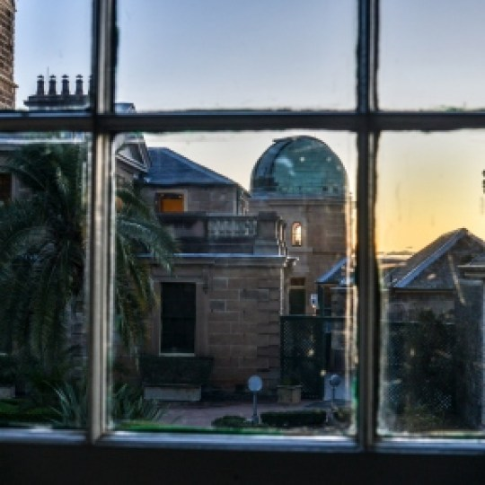 View of observatory dome at sunset through paned glass window.