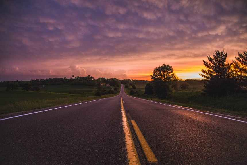 photo of empty road in between grass field during golden hour