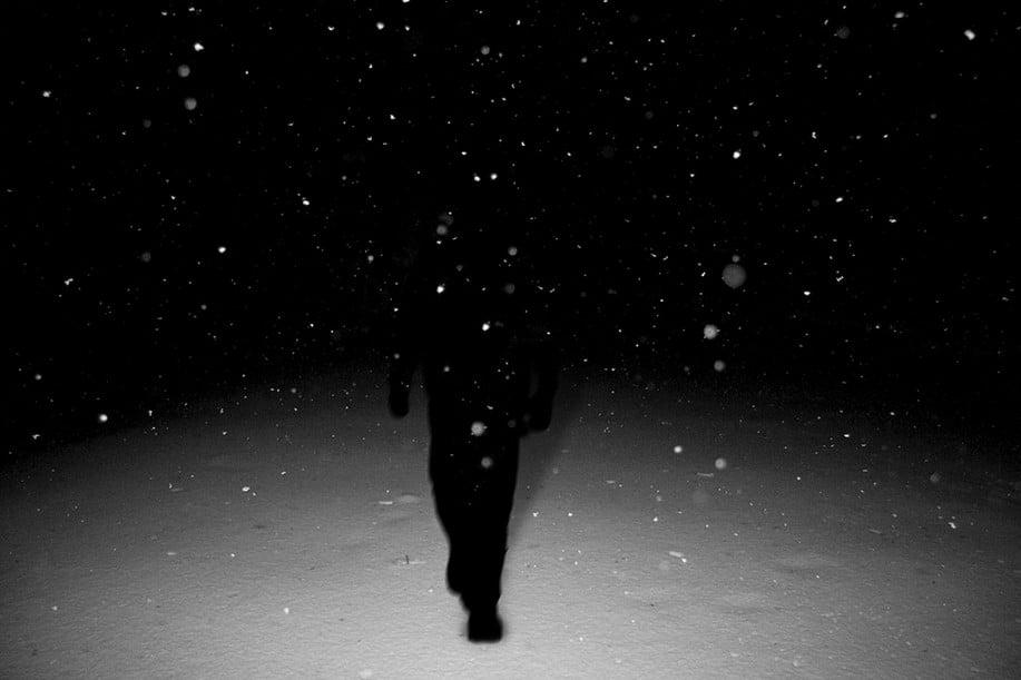 homme marche dans la neige la nuit