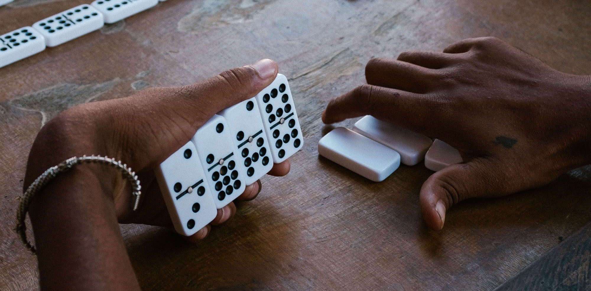 people playing dominos at a table